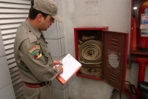 Imagem de arquivo mostra bombeiro vistoriando condições de extintor em estabelecimento comercial em Pelotas; convênio entre corporação e Sinduscon está mais perto de ser executado, diz comandante da guarnição