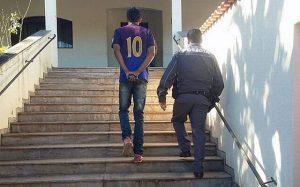 FOTO POSTADA POR POLICIAIS MILITARES EM QUE JOVEM É LEVADO À DELEGACIA