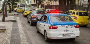 Policiais da PM seguram fuzis para fora da viatura em rua engarrafada na Lapa no centro do Rio de Janeiro